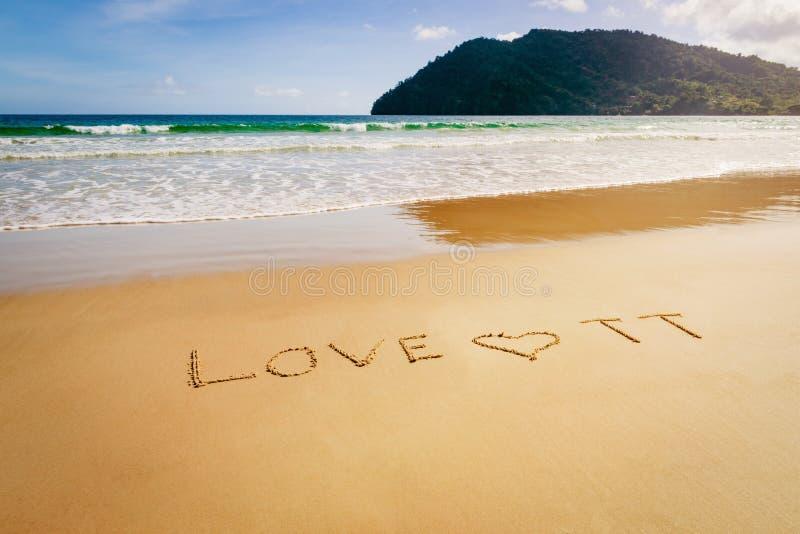 Redacte el amor TT Trinidad and Tobago escritos en la arena de la playa en playa de la bahía de Maracas imagenes de archivo