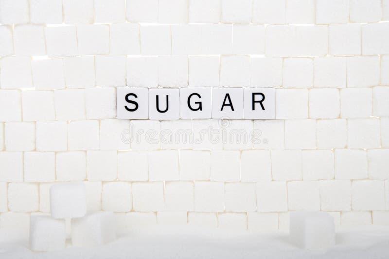 Redacte el AZÚCAR explicado con los cubos en una pared de los ladrillos del cubo del azúcar foto de archivo