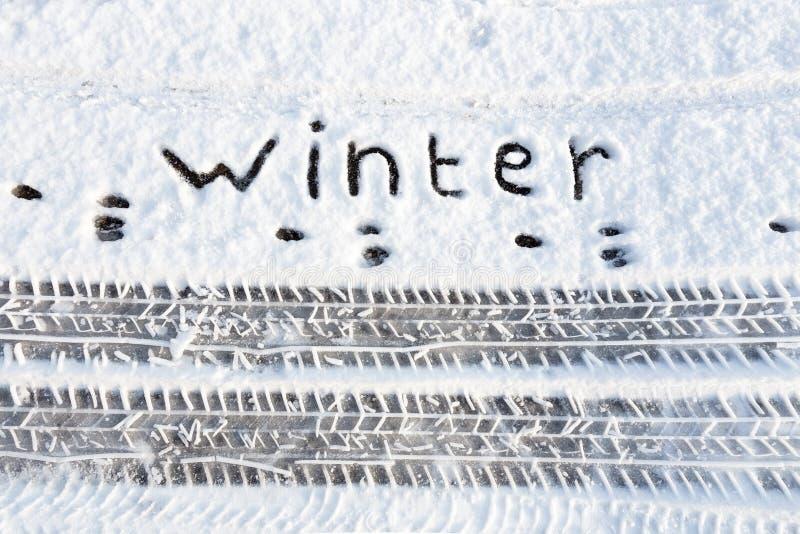 Redacte el invierno y las pistas del neumático en nieve en el camino foto de archivo