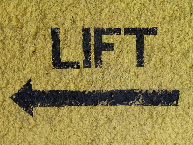 Redacte la ELEVACIÓN y la flecha pintadas en negro en la pared amarilla que señala en la dirección de la elevación/del elevador imágenes de archivo libres de regalías