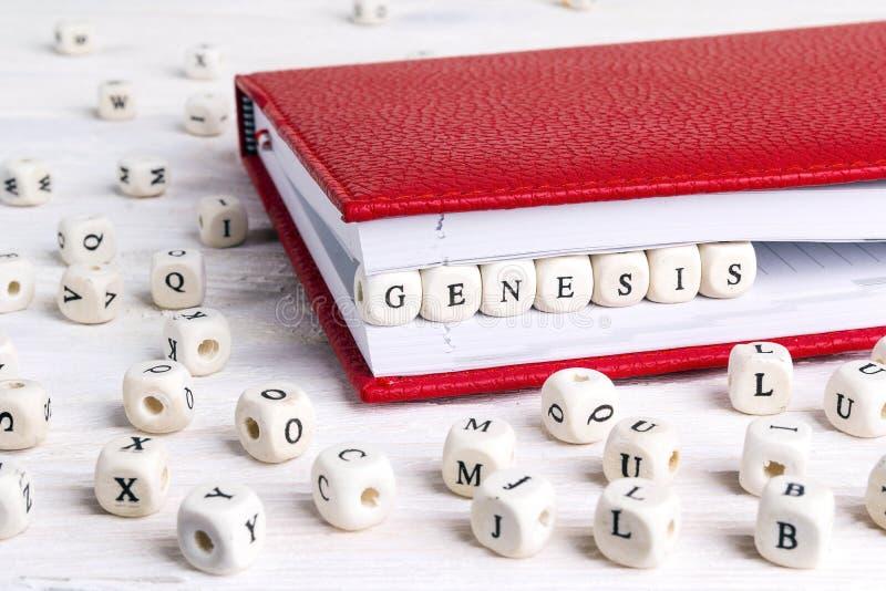 Redacte la génesis escrita en bloques de madera en cuaderno rojo en w blanco imagen de archivo