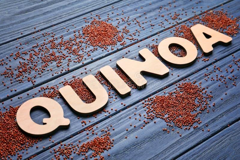Redacte la QUINOA hecha de letras y de semillas de madera imagenes de archivo