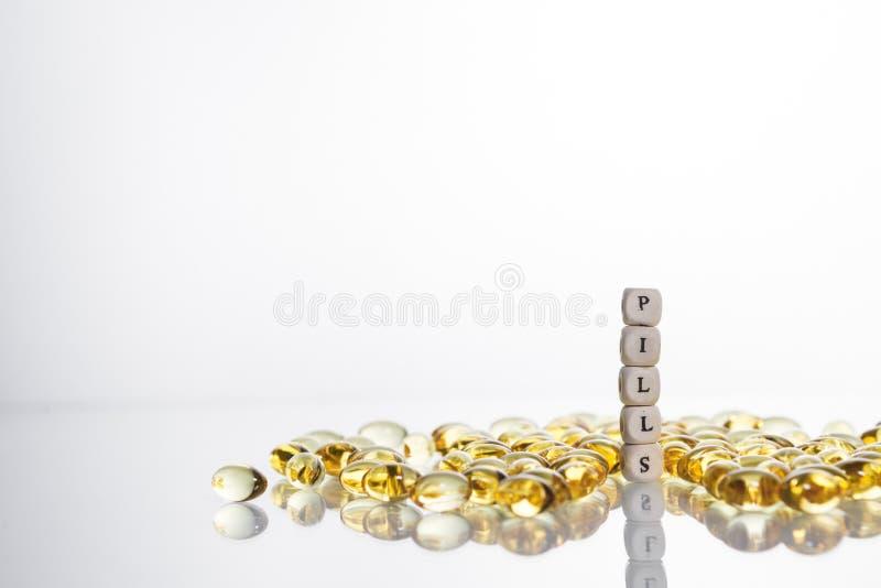 Redacte las píldoras de las letras de las píldoras de los cubos y del gel de la lecitina en l foto de archivo libre de regalías