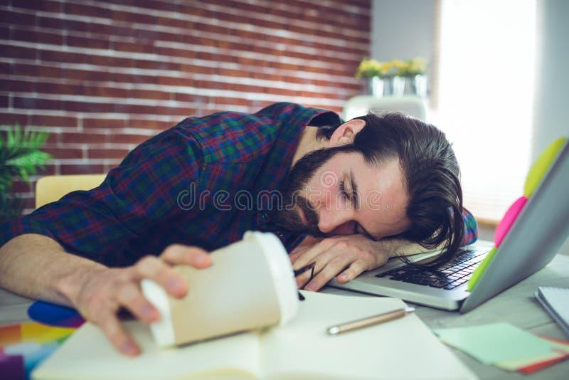 Redactor cansado que sostiene la taza disponible imagenes de archivo