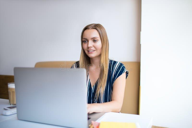 Redactor de anuncios experto sonriente feliz de la mujer que tiene videoconferencia vía el ordenador portátil mientras que se sie fotos de archivo