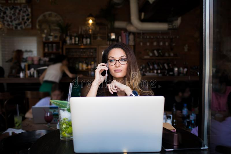 Redactor de anuncios femenino serio hermoso que habla vía el teléfono móvil durante trabajo sobre el dispositivo del red-libro foto de archivo