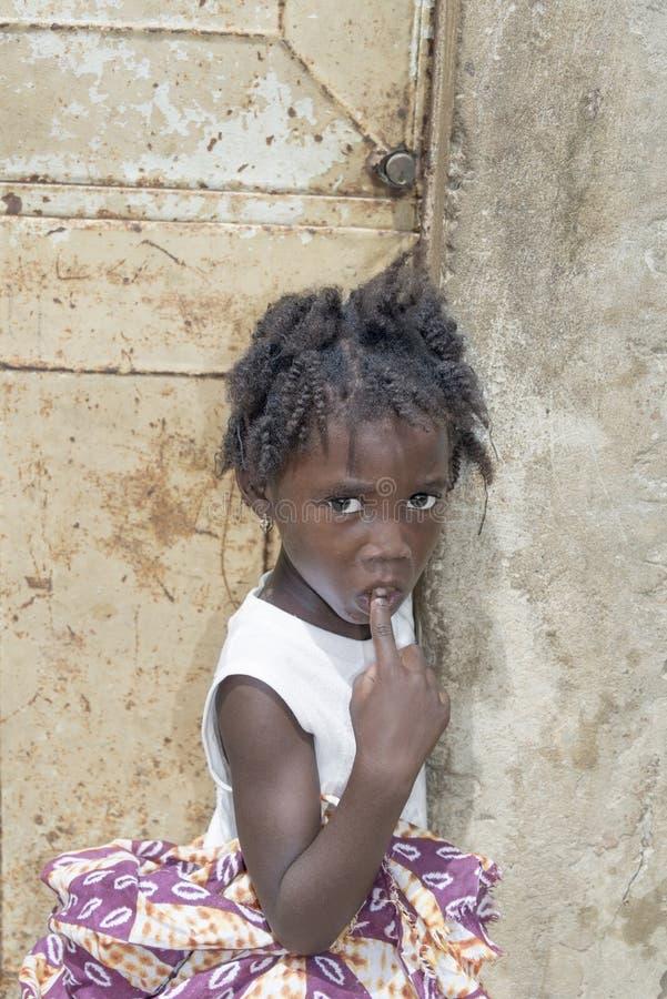 """Redaktörs- överskrift: THIAROYE oidentifierad senegalesisk flicka för SENEGAL, AFRIKA —JULI 26, 2014 †""""framme av en husdörr arkivbilder"""