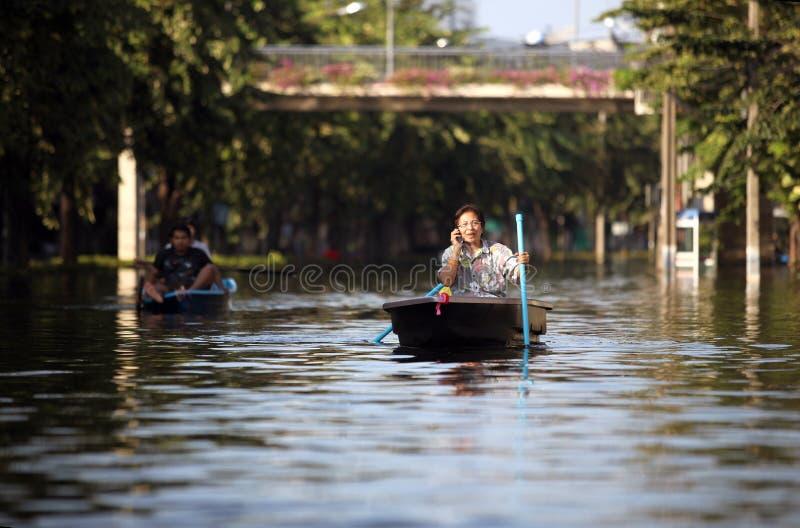Redaktörs- foto översvämmar i Thailand, en kvinna som svävar i fartyg och talar på hans mobiltelefon, Bangkok royaltyfri foto
