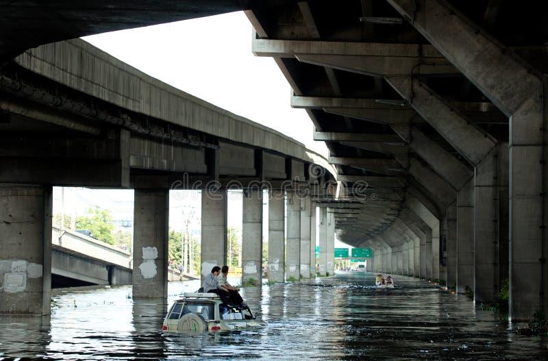 Redaktörs- foto som översvämmar i Bangkok, två män som sitter på taket av bilen för att fly från vattnet som fotograferas i 2011 arkivfoto