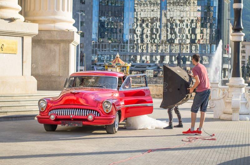 redaktörs- fotofors för brud i en gammal tidmätarebil för härlig röd tappning från sextio i ett centrum arkivfoton