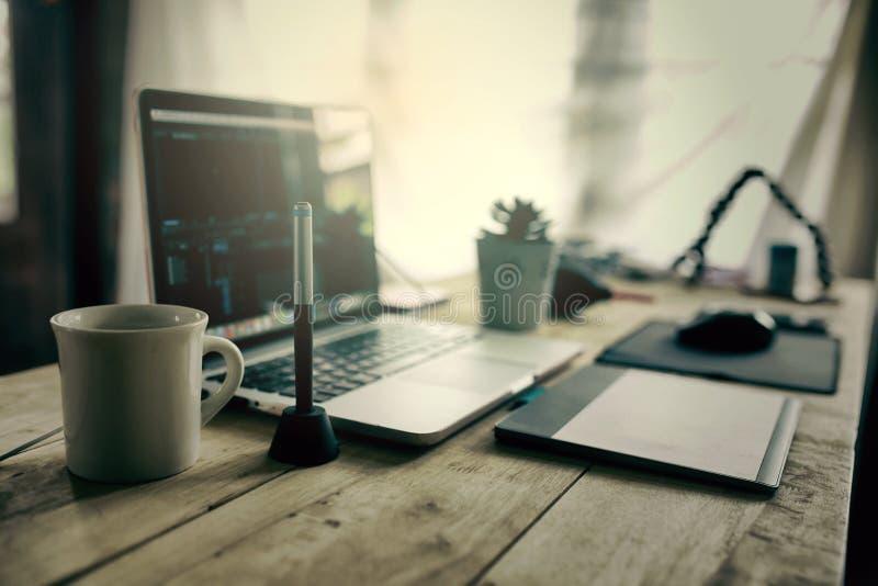 Redaktörskrivbordet för arbetande redigerande video levererar i regeringsställning bärbara datorn royaltyfria bilder