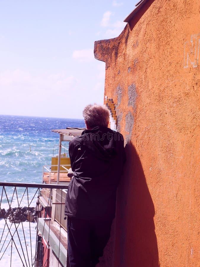 Redakt?rs- man som ser havet vid gammal strandbyggnad Riomaggiore Cinque Terre Italy royaltyfri foto