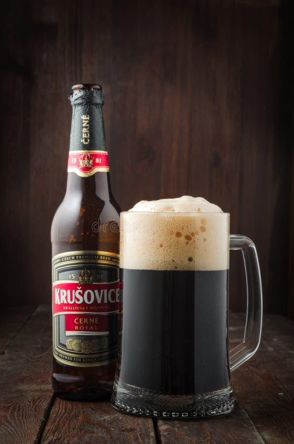 Redaktionelles Foto dunklen königlichen Bieres Krusovice mit Becher Bier auf dunklem hölzernem Hintergrund stockfoto