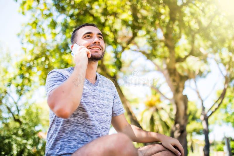 Redator especializado de sorriso que fala no telefone celular durante o trabalho da distância no laptop, sentando-se no parque da fotografia de stock