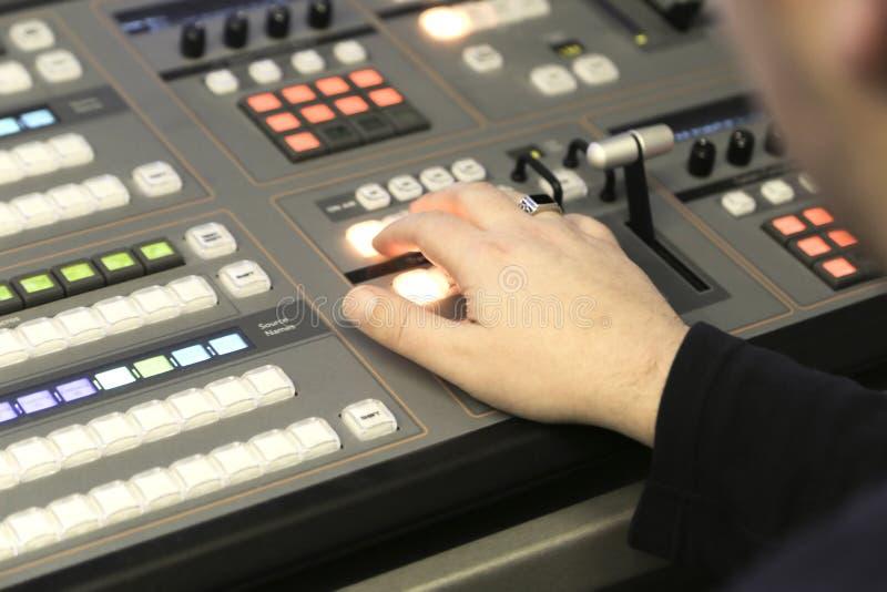 Redattore della TV che lavora con l'audio video miscelatore in un broadca della televisione immagini stock