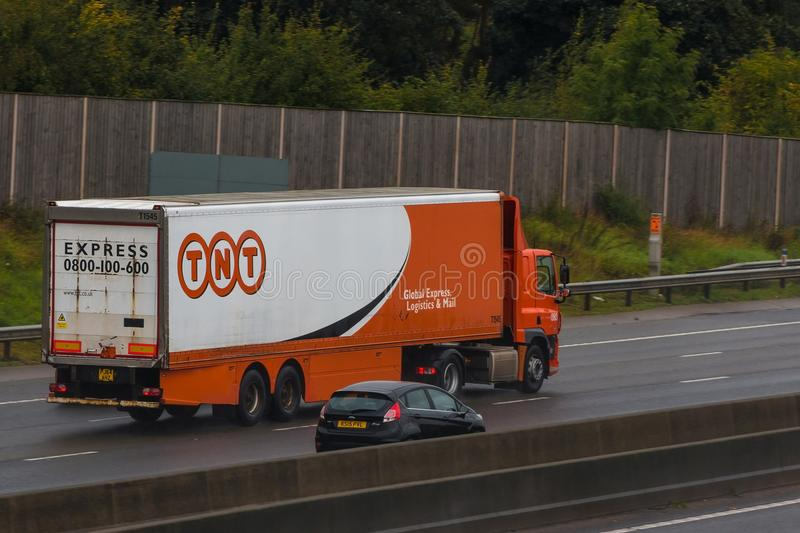 TNT lorry in motion. Redbourn, UK - September 21, 2017: Lorry belonging to TNT Express international courier delivery services company in motion on the British royalty free stock photos
