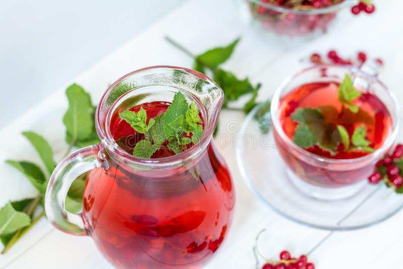 Redcurrant ποτό στη διαφανή καράφα και το φλυτζάνι γυαλιού στοκ φωτογραφίες