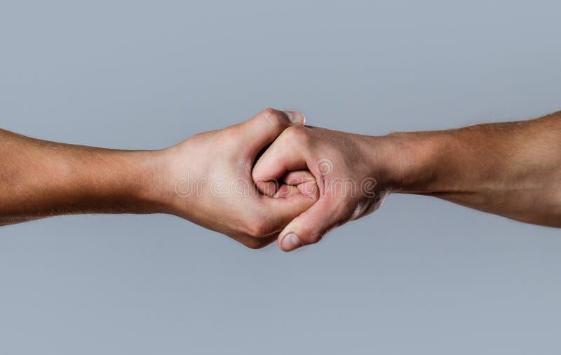 Redding, die hand helpen Mannelijke die hand in handdruk wordt verenigd De handen van de mensenhulp, voogdij, bescherming Twee ha royalty-vrije stock foto's
