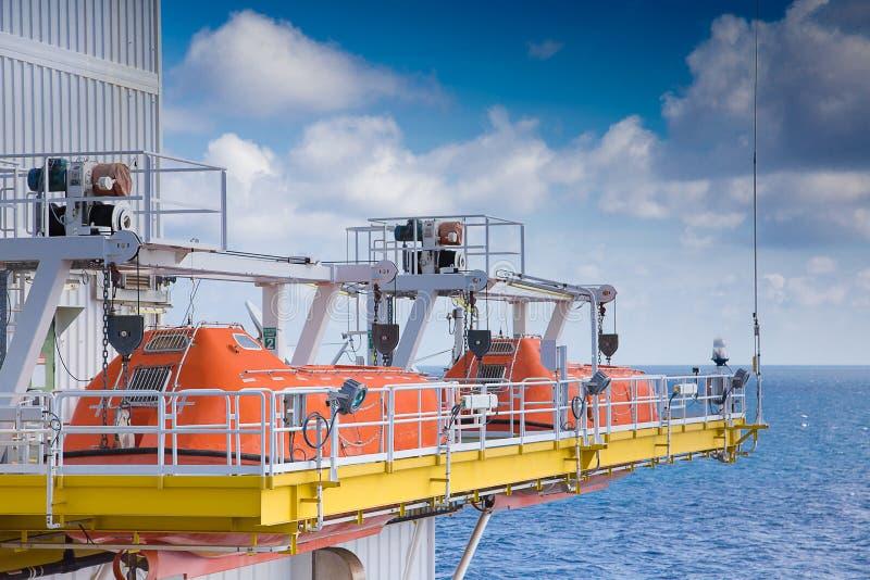 Reddingsboottribune langs op verzamelingspunt van olie en gasplatform royalty-vrije stock afbeelding