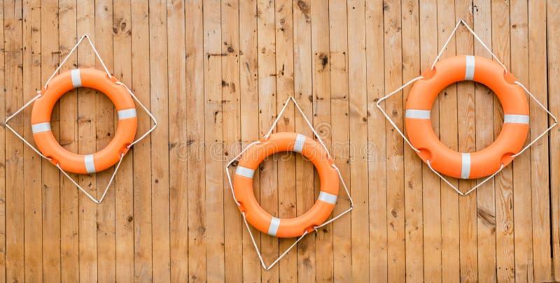 Reddingsboten die op een muur van houten planken bij de kust hangen stock foto's