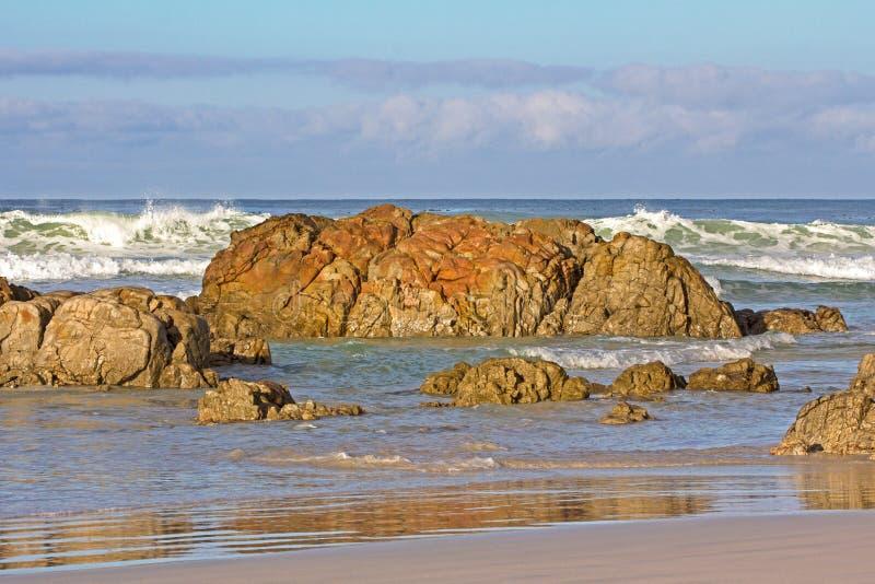 Reddish Brown Rocks on Beach royalty free stock photo