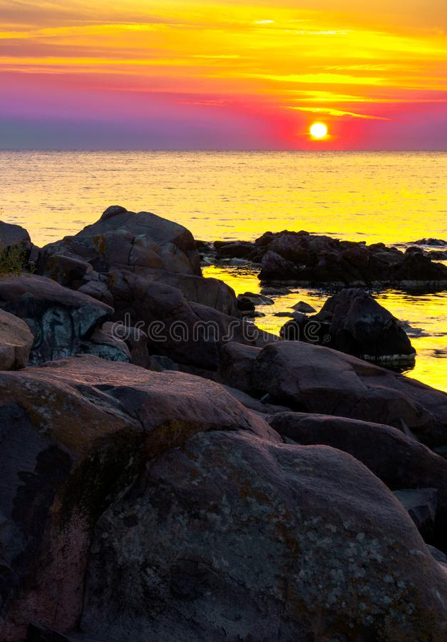 Reddish sunrise over the sea with rocky shore. Beautiful summer scenery and vacation concept royalty free stock photos