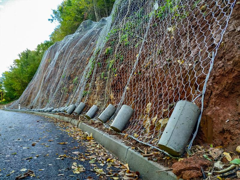 Rede de fio colocada em colina rochosa como prevenção contra rochas que caem na estrada e prevenção de acidentes durante a conduç fotos de stock