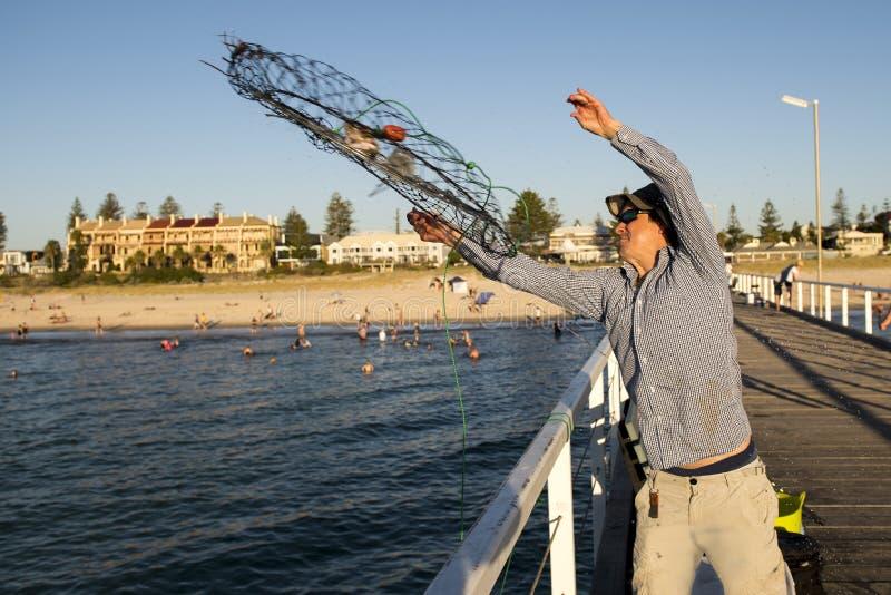 Rede de jogo nova da cesta dos peixes e dos caranguejos do pescador atrativo feliz e orgulhoso no por do sol da doca do mar na pe fotografia de stock