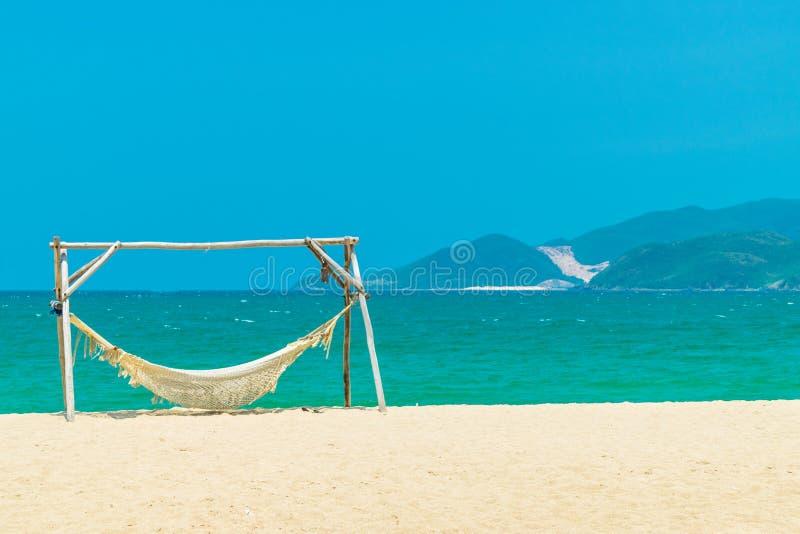 Rede de madeira na praia com areia amarela e fundo verde da ilha foto de stock royalty free