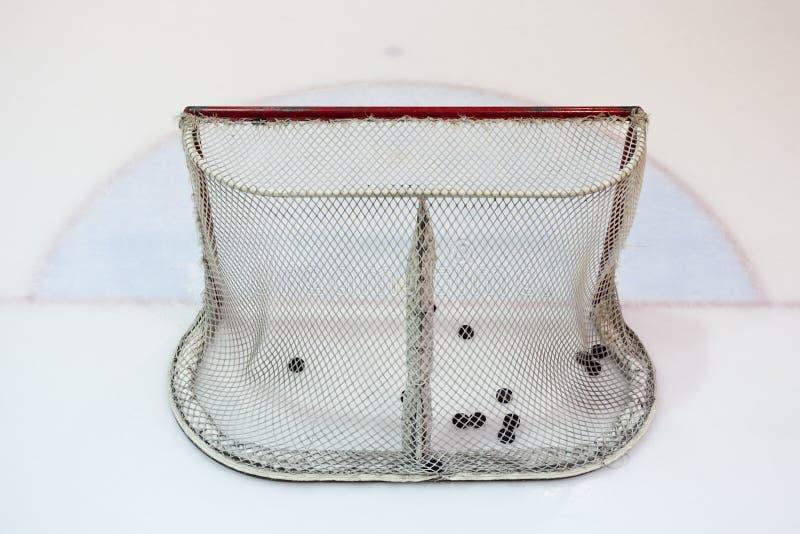 Rede do hokey do gelo enchida com os discos fotos de stock