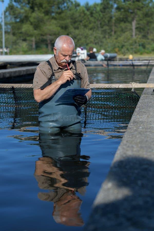 Rede dos peixes da fixação do homem do pescador fotografia de stock