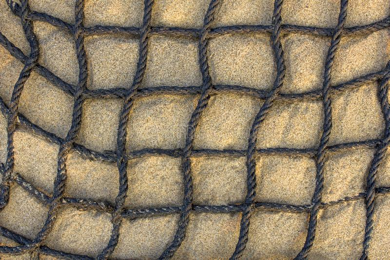 Rede quadriculado grossa preta do cabo na opini?o superior da areia clara Textura da superf?cie ?spera imagens de stock royalty free