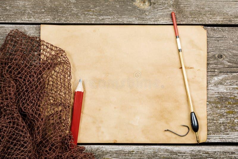 Rede velha do papel, de pesca e a pesca do flutuador, ganchos em um tabl de madeira imagens de stock royalty free