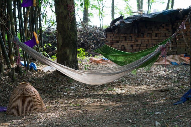 Rede velha que pendura na árvore no lugar desarrumado velho do campo em Vietname Quebrando o lugar do resto para o fazendeiro imagens de stock