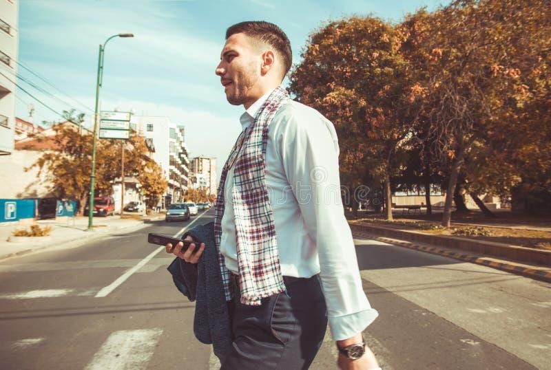 Redegewandter Geschäftsmann, der in die Stadt geht und seinen Mantel und Telefon hält lizenzfreie stockbilder
