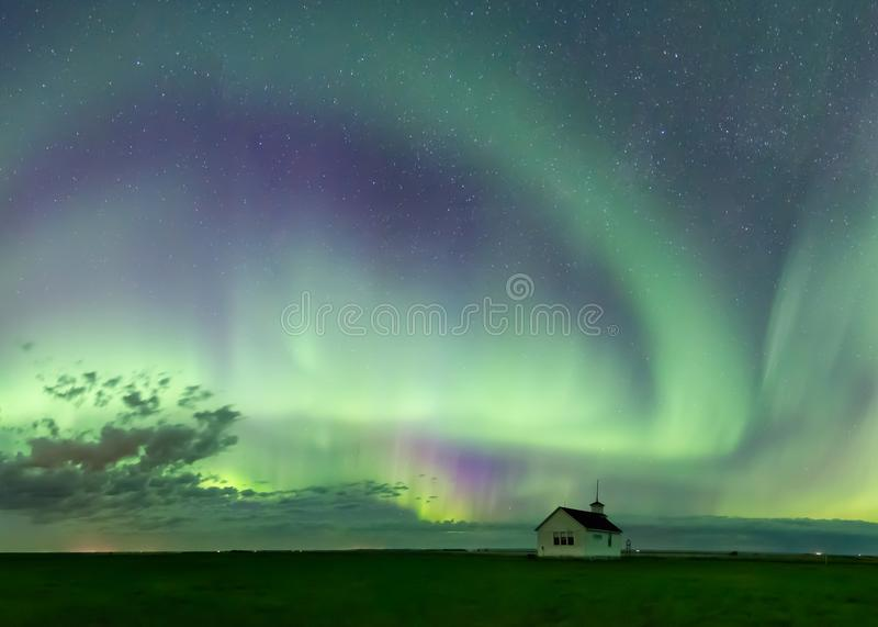 Redemoinho de Aurora Borealis Northern Lights sobre a escola histórica perto de Kyle, Saskatchewan, Canadá imagens de stock royalty free