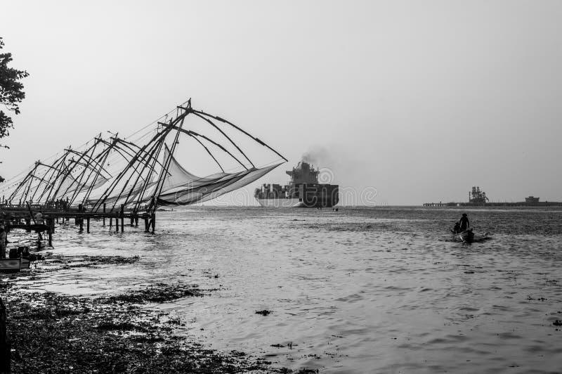 Redes de pesca chinas en Cochi, Kerala, la India, con el buque de Cotainer en fondo imagen de archivo libre de regalías