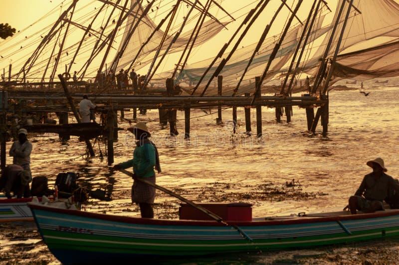 Redes de pesca chinas en Cochi, Kerala, la India - pescadores en primero plano Colores del ocaso imágenes de archivo libres de regalías