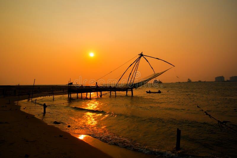 Redes de pesca chinesas de Kochi e o barco com os pescadores no por do sol foto de stock