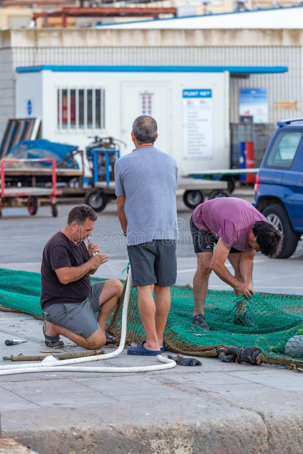 Redes de pesca do reparo do pescador no porto Palamos 07 12 2019, Espanha imagens de stock