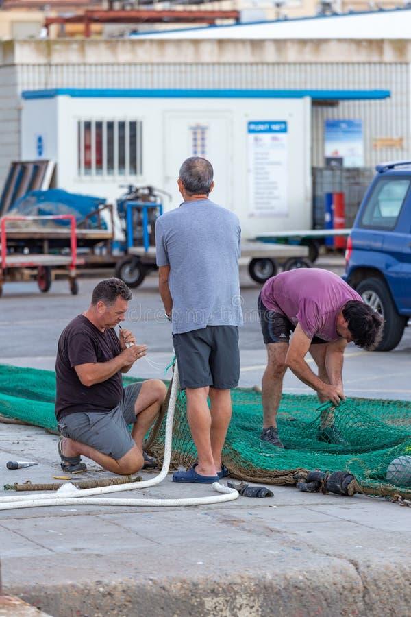 Redes de pesca de la reparación del pescador en el puerto Palamos 07 12 2019, España imagenes de archivo