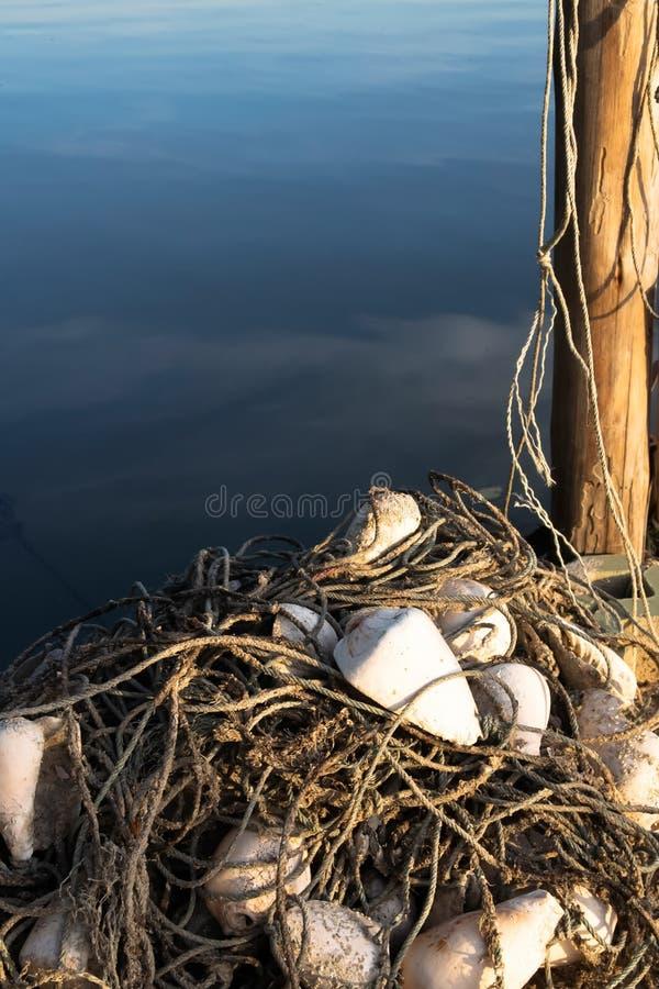 Redes, equipo de pesca que fue colocado al lado de los pilares de madera en el mar imágenes de archivo libres de regalías