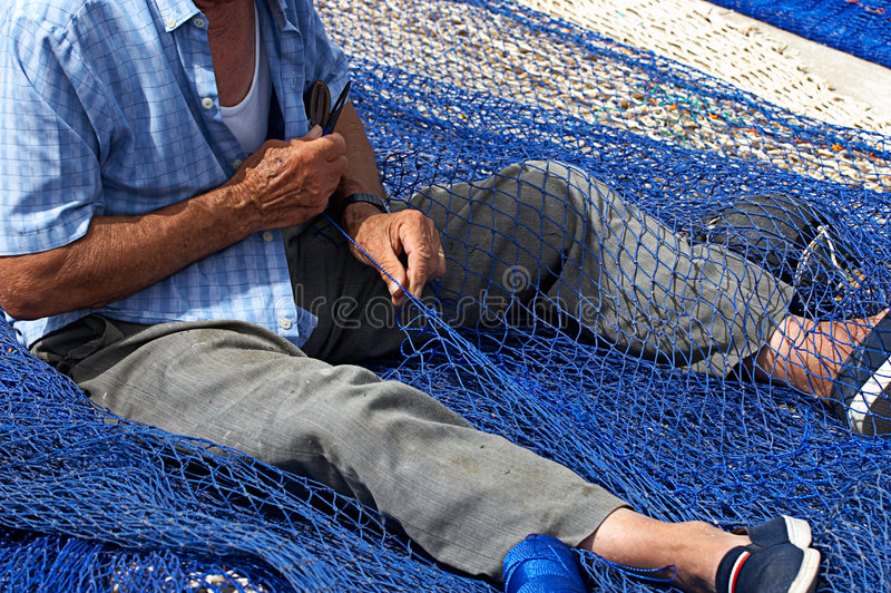 Redes velhas da emenda do pescador imagens de stock royalty free