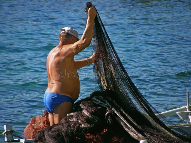 Redes velhas do pescador e dos peixes imagens de stock