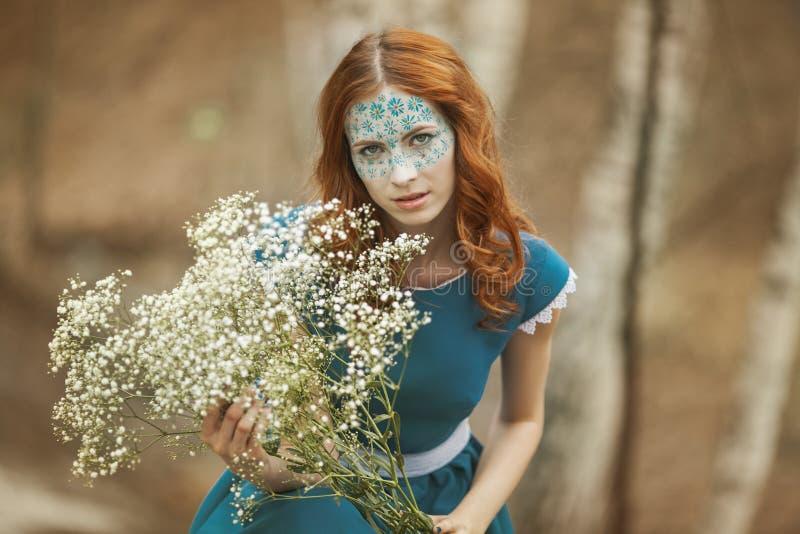 redhair女孩画象蓝色礼服的有婴孩的呼吸的在春天森林开花 免版税库存图片