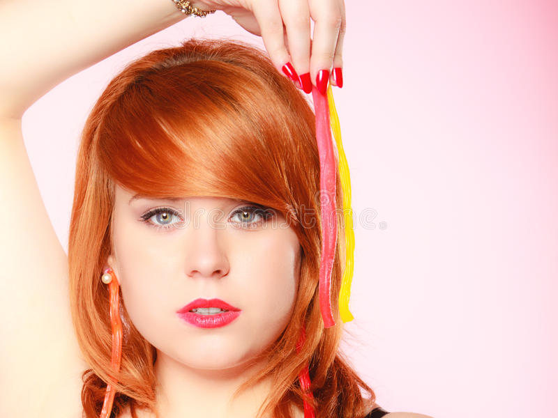 Redhair girl holding sweet food jelly candy on pink. stock image
