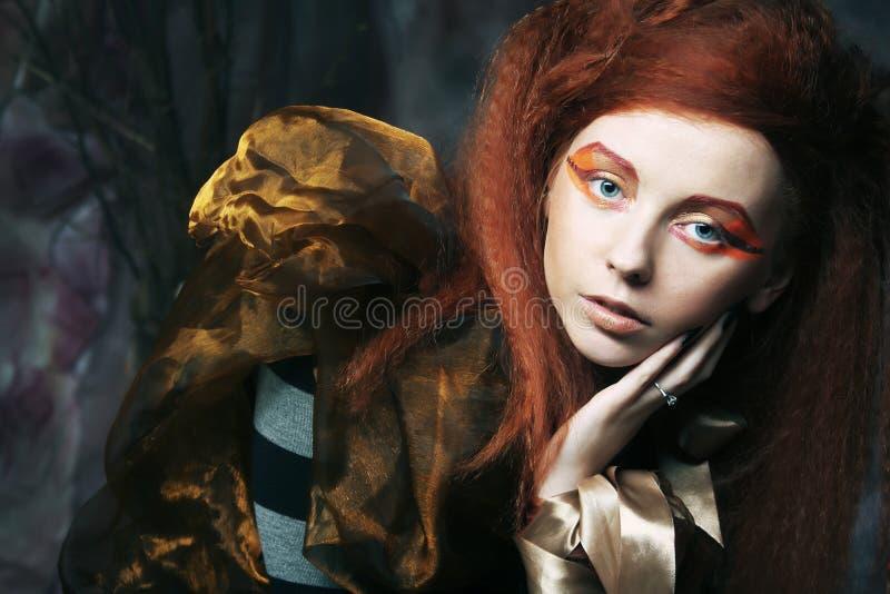 Redhair kvinna med ljust idérikt smink royaltyfria foton