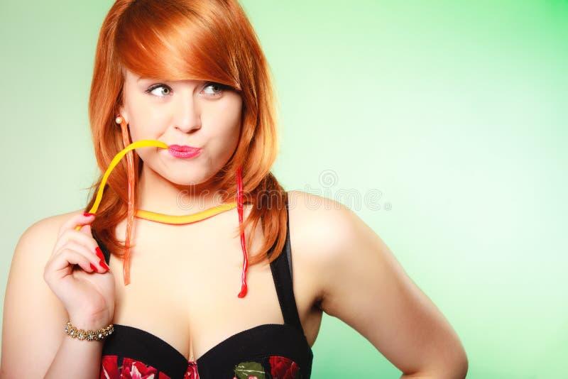 Redhair-Mädchen, das süße Lebensmittelgeleesüßigkeit auf Grün hält stockbilder