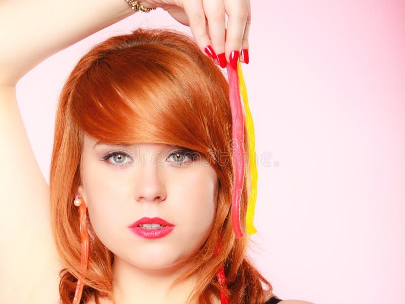 Redhair-Mädchen, das süße Lebensmittelgeleesüßigkeit auf Rosa hält stockbild