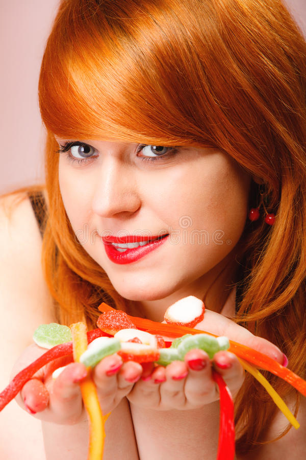 Redhair-Mädchen, das süße Lebensmittelgeleesüßigkeit auf Rosa hält stockfotos